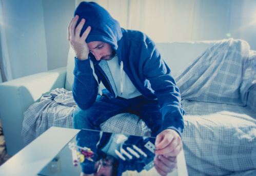 istock sad man doing snorting cocaine at home on his own 505393555