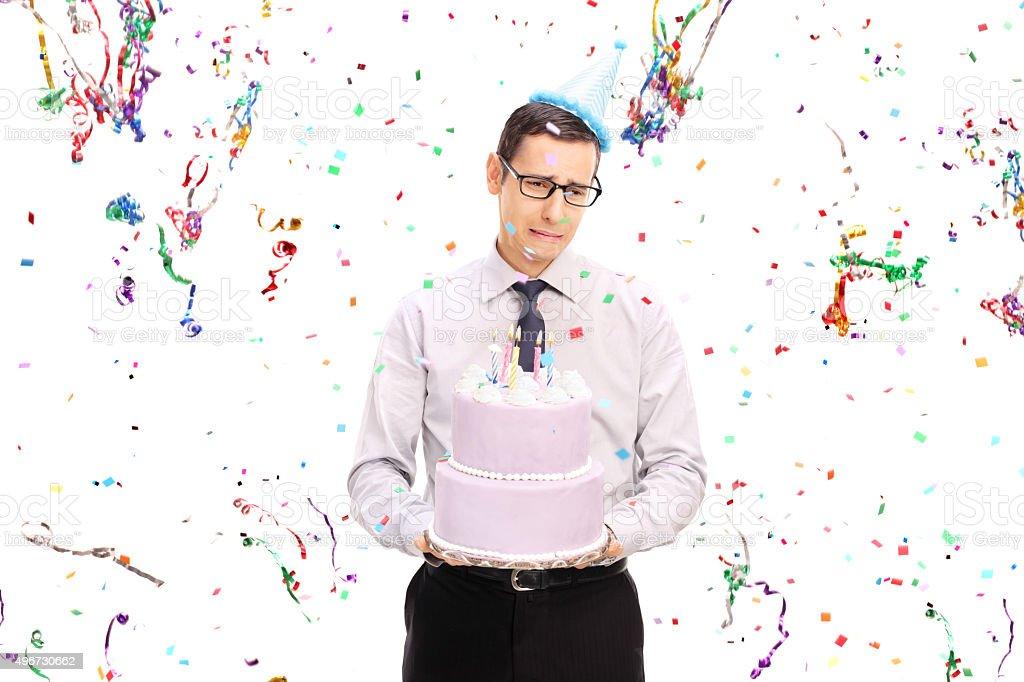 Sad man holding a birthday cake and crying stock photo