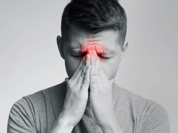 droevige mens die zijn neus houdt omdat de pijn van de sinus - bijholte stockfoto's en -beelden