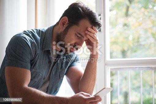 istock Sad man holding phone alone at home 1093988652