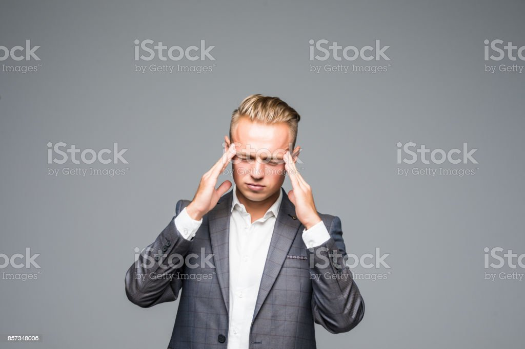 Sad man in gray suit touching his temples because of suffering from migraine on gray background stock photo