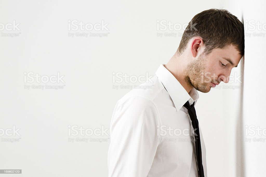 Sad man leaning against a wall. royalty-free stock photo