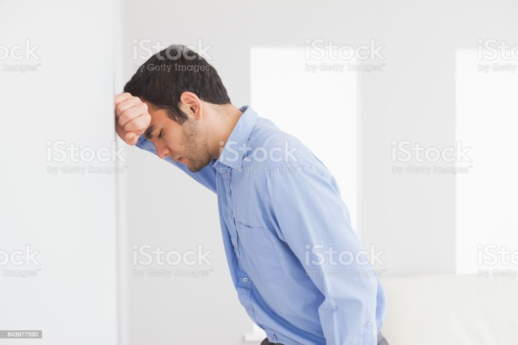Sad man leaning his head against a wall stock photo