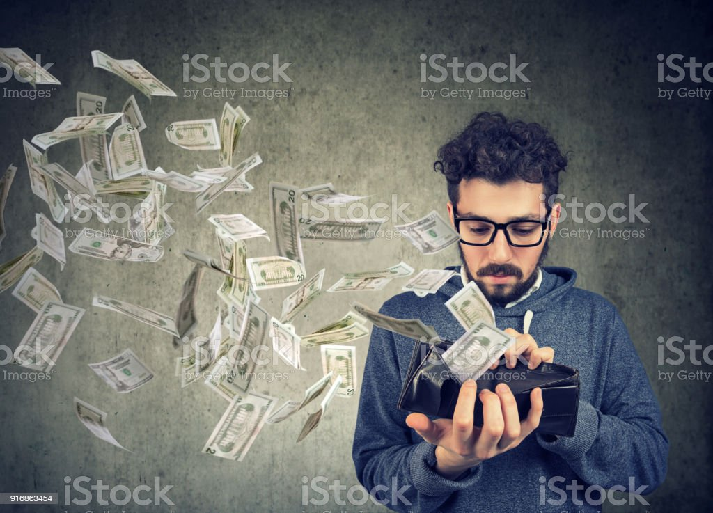 Sad man looking at his wallet with money dollar banknotes flying out away stock photo
