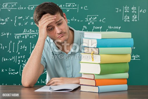 istock Sad Man Looking At Stack Of Books 600674698