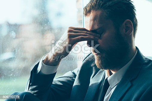 istock Sad man looks depressed and covers his eyes 509710778