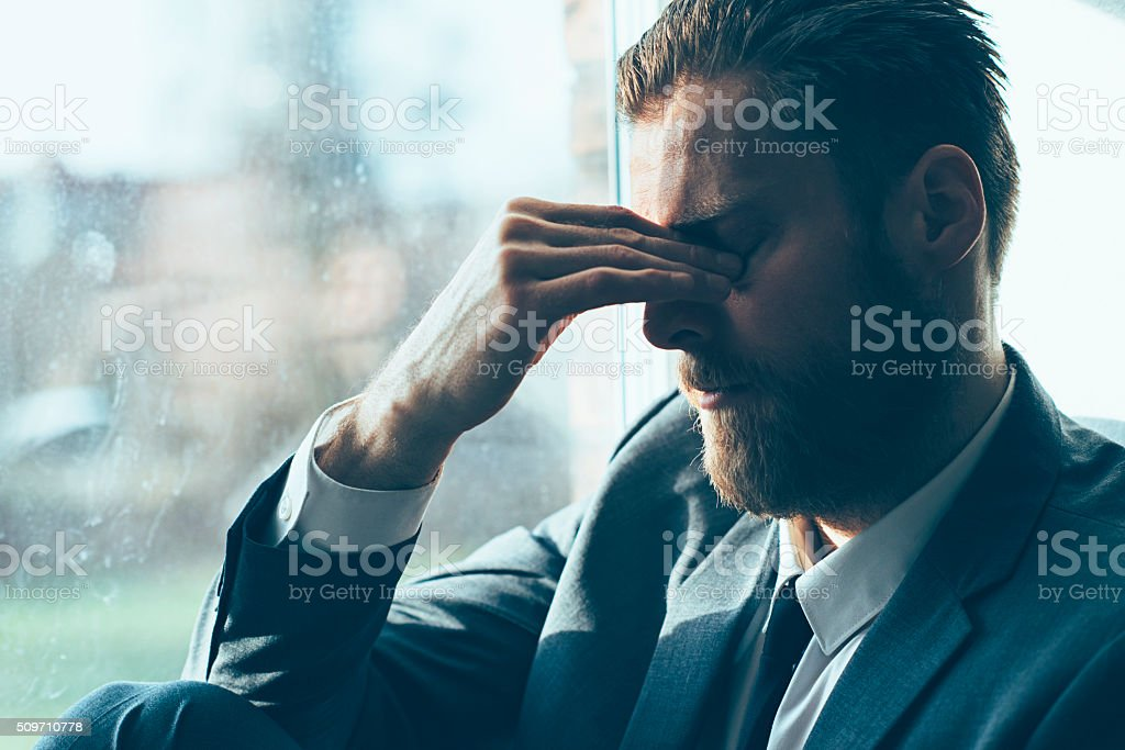 Sad man looks depressed and covers his eyes stock photo