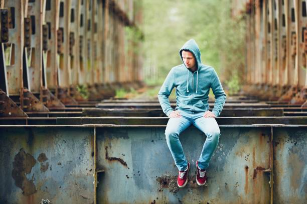 Sad man on the abandoned bridge stock photo