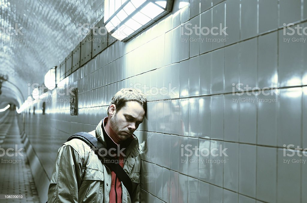 Sad Man Resting Head Against Tunnel Wall royalty-free stock photo