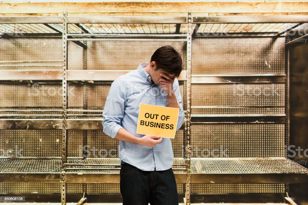 Sad man showing that his business has failed and is now closed