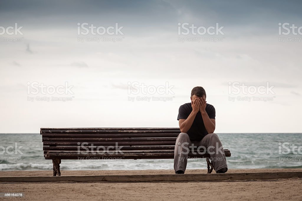 Sad man sits on old wooden bench on sea coast stock photo