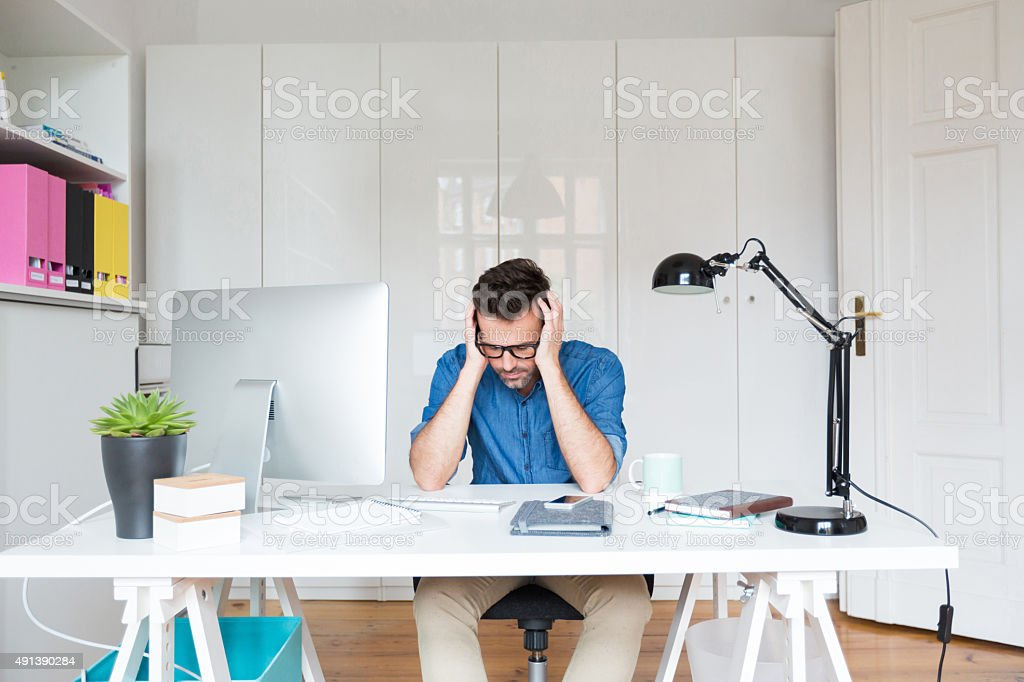 Sad man sitting at the desk with head in hands Front view of a sad man sitting at the desk in an office with head in hands. Computer on the desk. 2015 Stock Photo