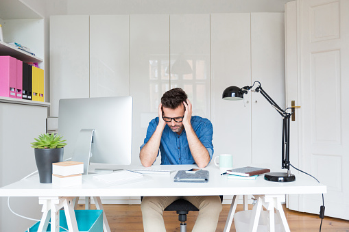 Sad Man Sitting At The Desk With Head In Hands Stock Photo - Download Image Now