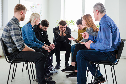 Sad Man Sitting In Group Therapy At Lecture Hall Stock Photo - Download Image Now