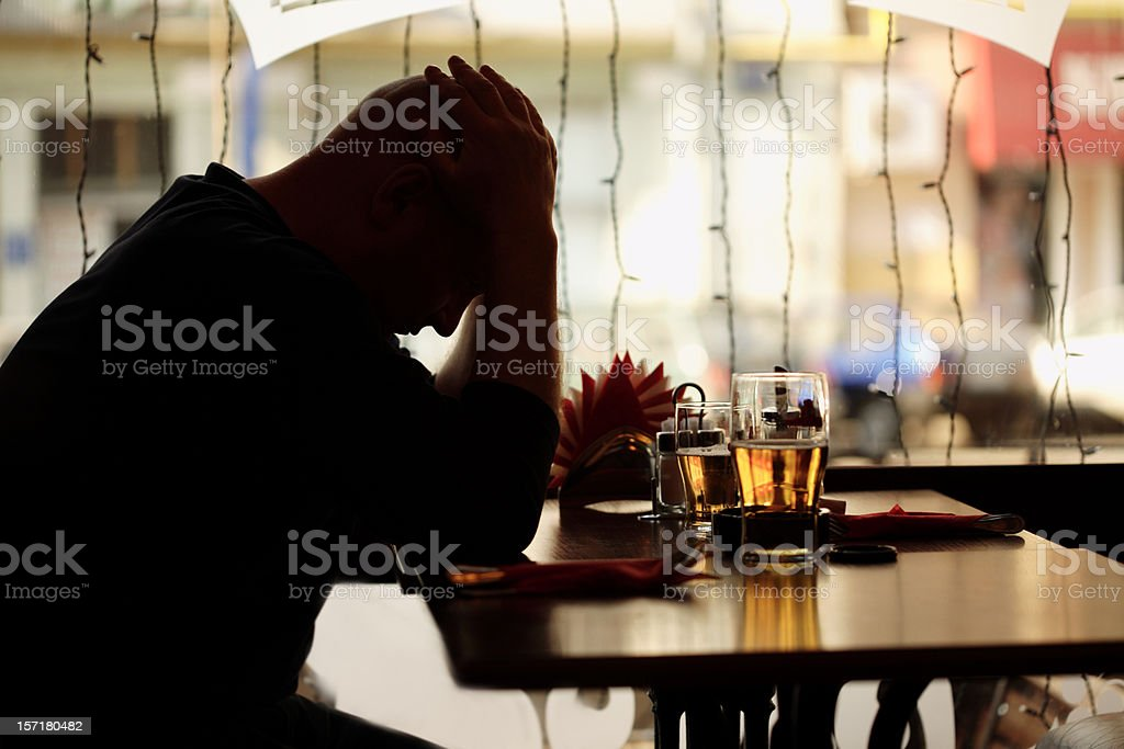 sad man sitting in restaurant stock photo