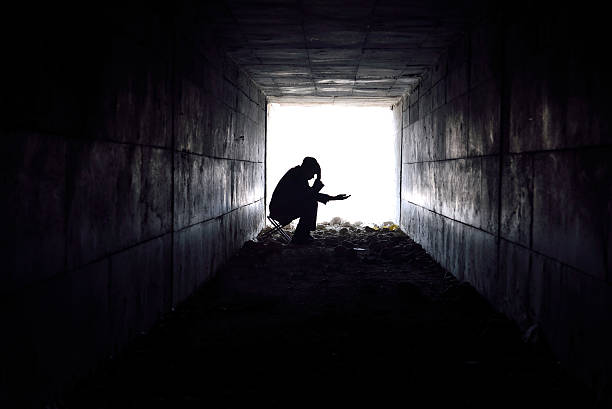 trauriger mann sitzen in den tunnel - bettler stock-fotos und bilder