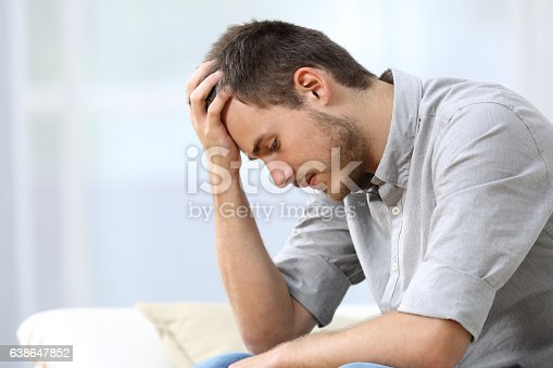istock Sad man sitting on couch at home 638647852