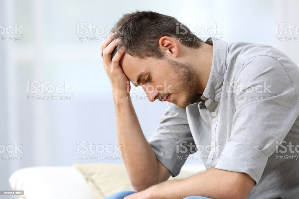 Sad man sitting on couch at home stock photo