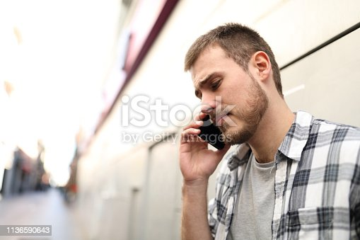 istock Sad man talking on phone in the street 1136590643