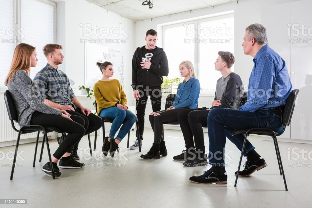 Sad man talking while friends and worker listening Sad young man talking while friends and therapist listening. Men and women are solving problems in group therapy session. They are wearing casuals. 18-19 Years Stock Photo