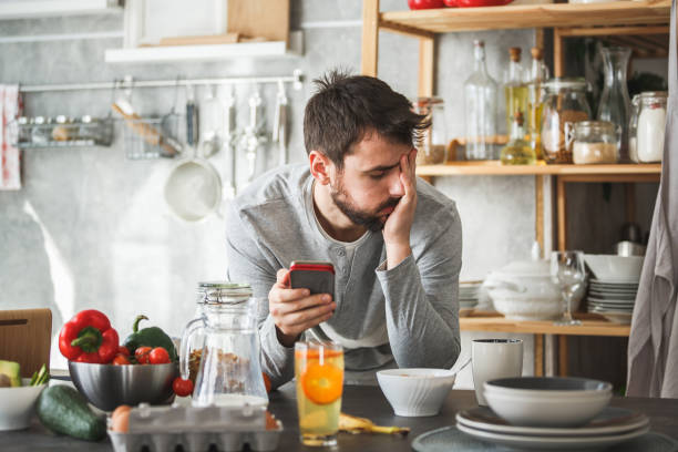 Sad man using smart phone during breakfast at home Front view of a young man looking sad while using smart phone at home. He is having breakfast at the kitchen counter. head in hands stock pictures, royalty-free photos & images