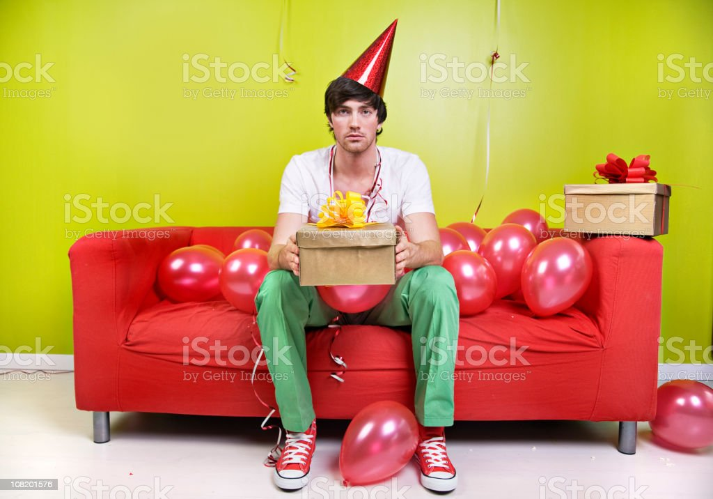 Sad Man Wearing Party Hat Holding Present with Balloons stock photo