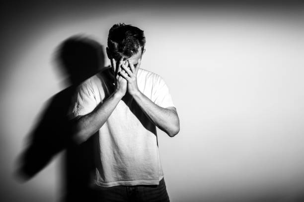 sad man with hands on face in sadness, on white background, black and white photo, free space stock photo