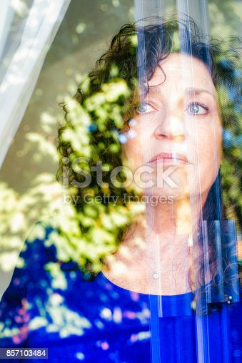 543048812 istock photo Sad mature Caucasian female looking out of a window 857103484