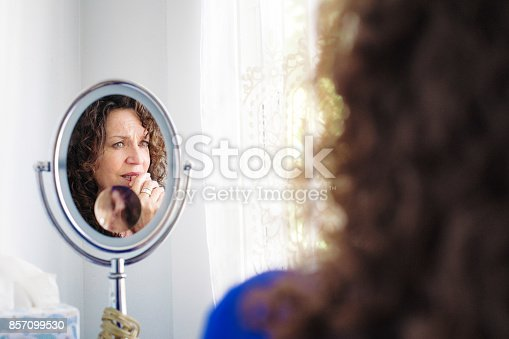 543048812 istock photo Sad Mature Caucasian female sitting in front of mirror stressing out 857099530
