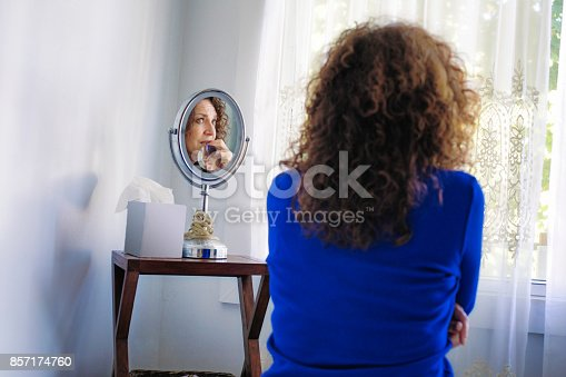543048812 istock photo Sad Mature Caucasian female sitting in front of window stressing out 857174760
