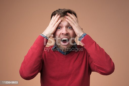 626964348istockphoto Sad mature man holding his head in hands and screaming 1153649853