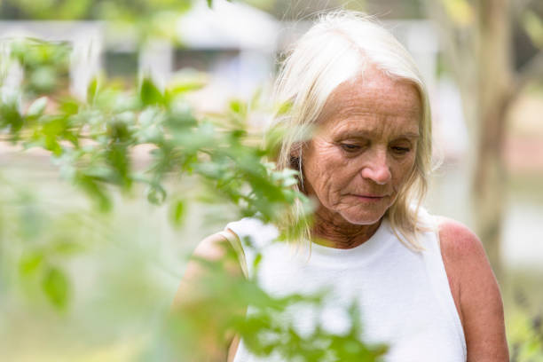 Sad mature woman walking in the park, copy space stock photo