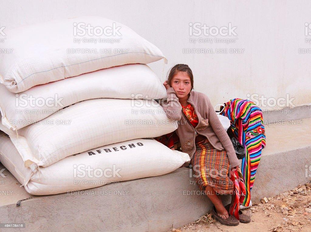 Sad Mayan Girl leaning on the sacks stock photo