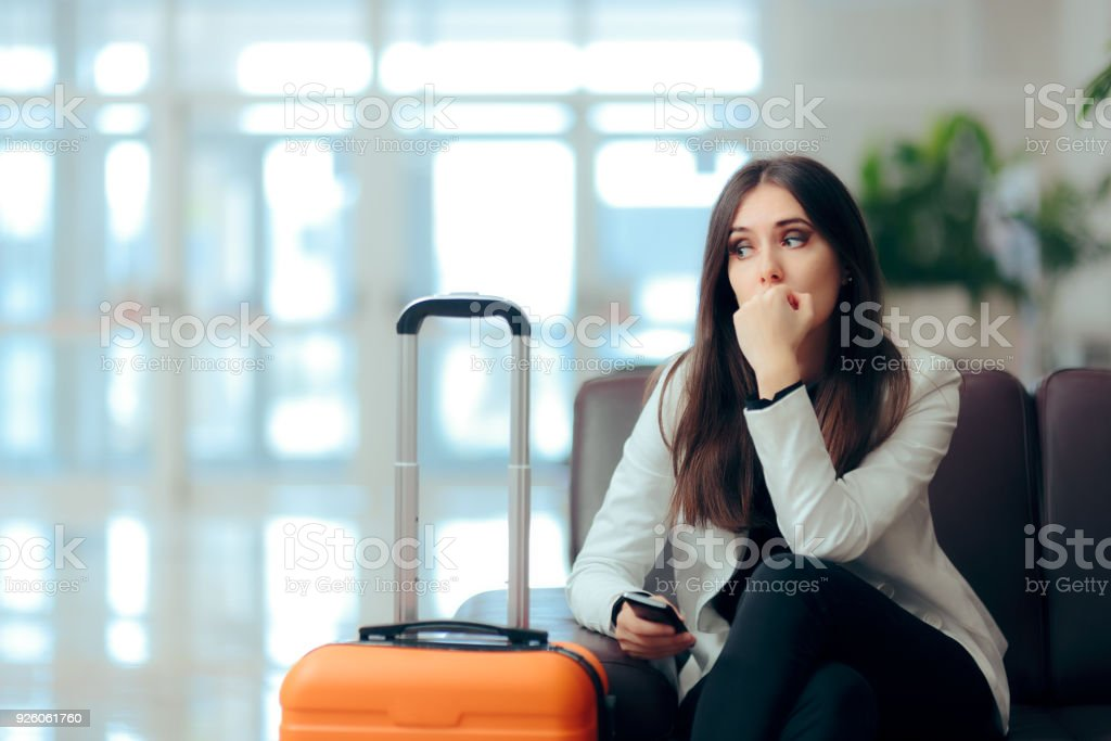 Sad Melancholic Woman with Suitcase in Airport Waiting Room stock photo