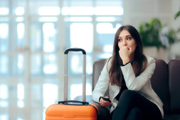 traurige, melancholische frau mit koffer im flughafen wartezimmer - bedauern stock-fotos und bilder