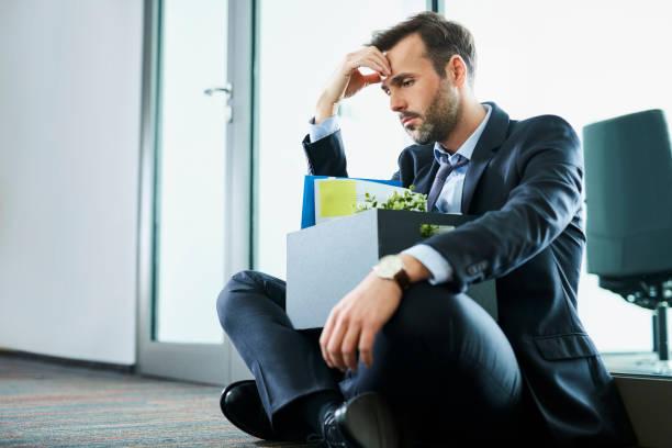 traurig im mittleren alter geschäftsmann sitzt mit seinen persönlichen habseligkeiten nach seinen job zu verlieren - stellenabbau stock-fotos und bilder