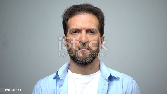 Sad middle-aged man looking into camera, unemployment, social insecurity