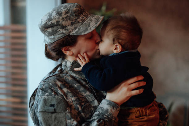Sad military soldier says goodbye to her son stock photo