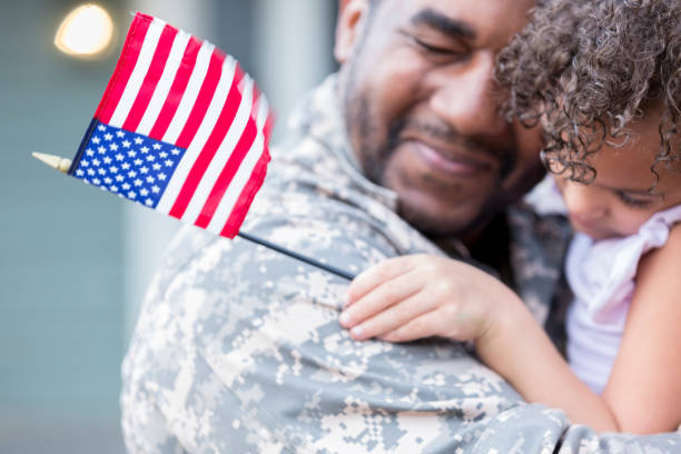 Sad military soldier says goodbye to his little girl Upset soldier holds his little girl tight while saying goodbye to her. He is leaving for long overseas assignment. military lifestyle stock pictures, royalty-free photos & images