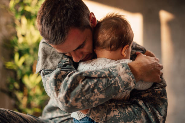 Sad military soldier says goodbye to his son stock photo
