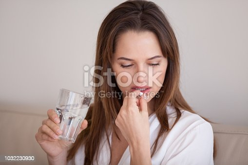 istock Sad millennial woman taking pill to cure pain or depression 1032230930