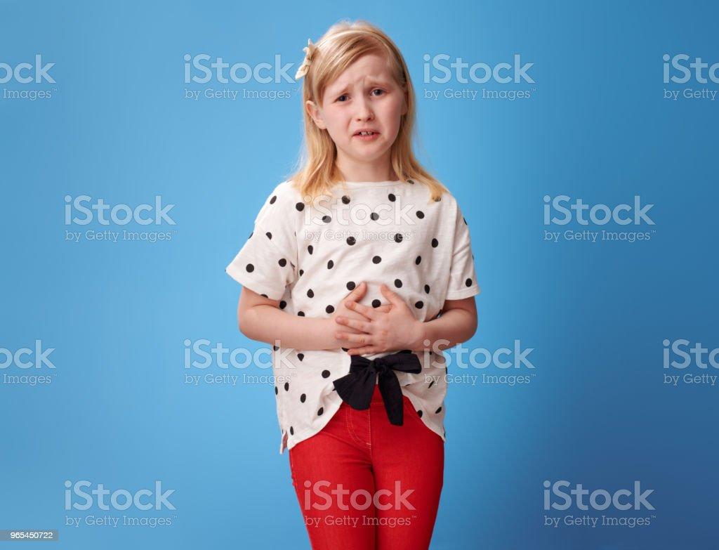 哀傷的現代孩子在紅色褲子藍色與腹部痛苦 - 免版稅一個人圖庫照片