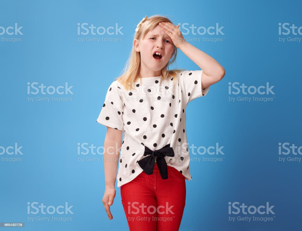 sad modern child in red pants on blue with headache zbiór zdjęć royalty-free