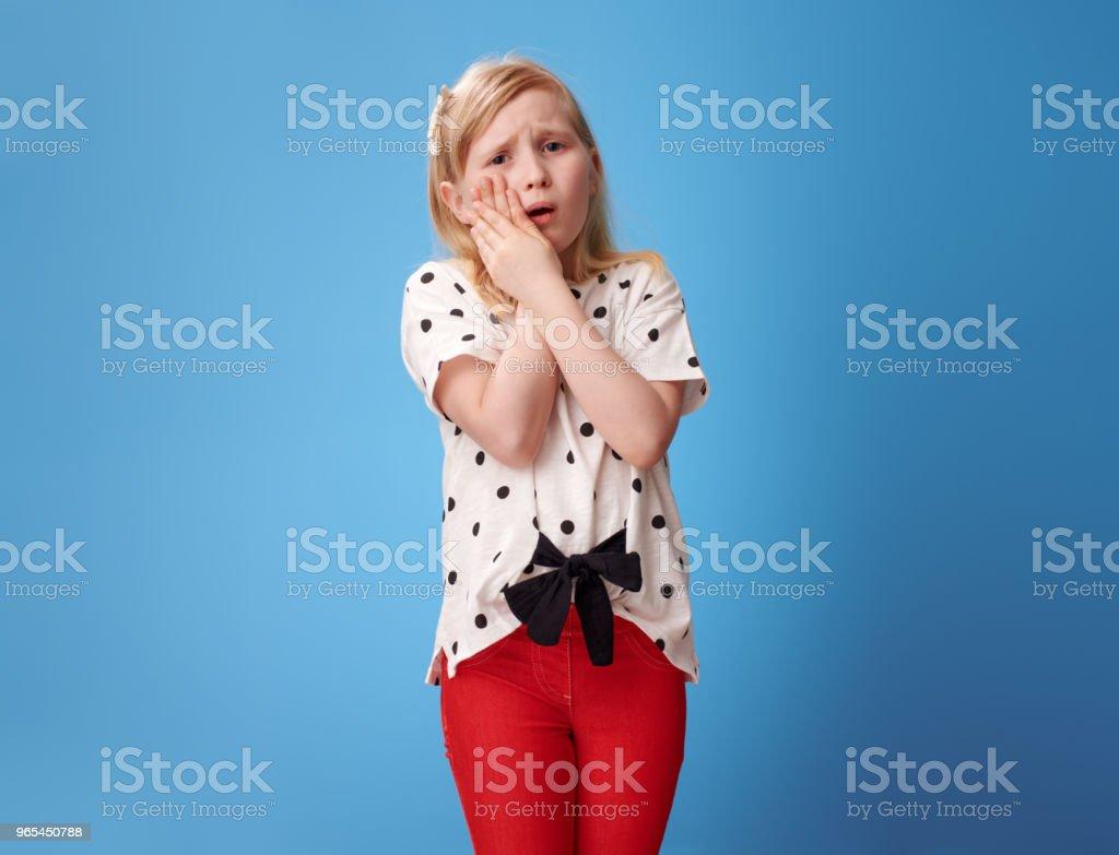 jeune fille moderne triste dans un pantalon rouge sur bleu avec des maux de dents - Photo de Alimentation lourde libre de droits