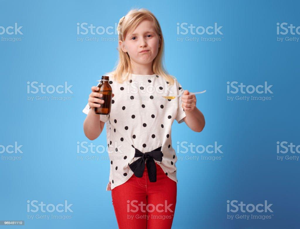 sad modern girl taking spoon of children's suspension on blue zbiór zdjęć royalty-free