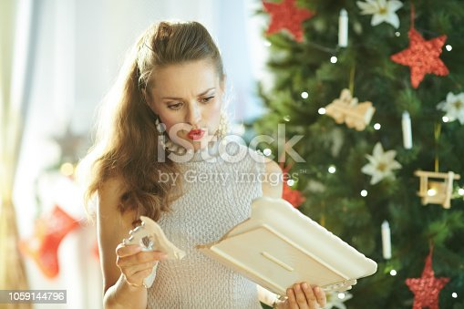 1059144984 istock photo sad modern housewife near Christmas tree looking at broken dish 1059144796