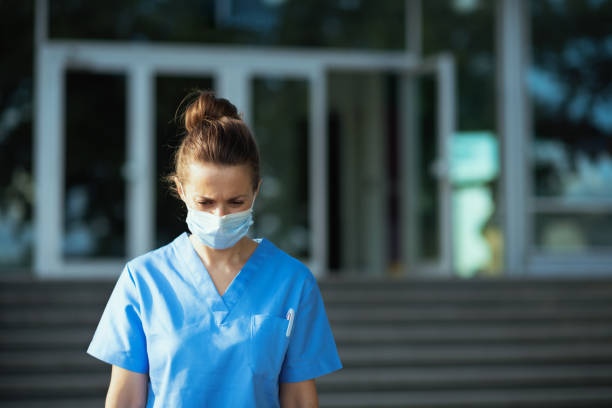 sad modern medical practitioner woman outside near clinic stock photo