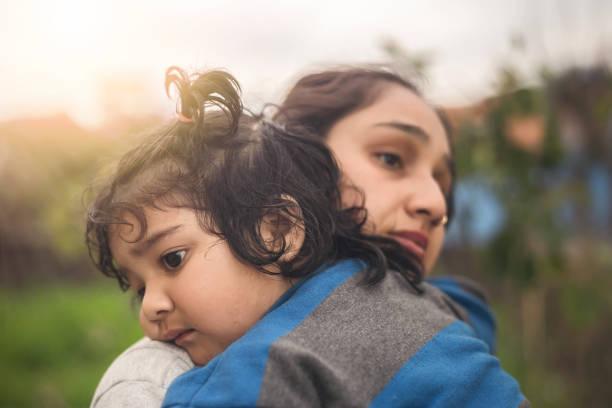 Traurige Mutter umarmt ihre kleine Tochter im Freien – Foto