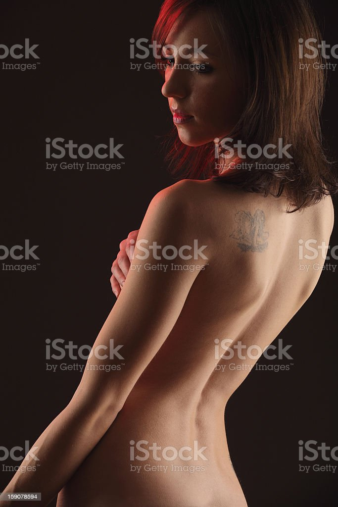Sad naked woman looking over her left shoulder royalty-free stock photo