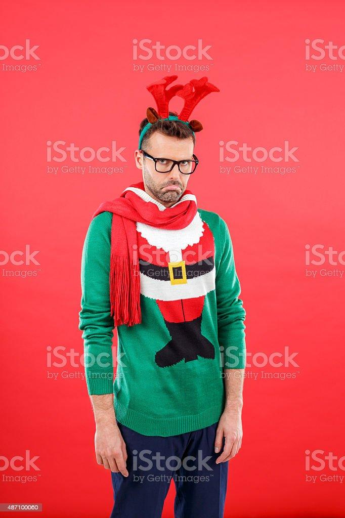 Studio portrait of sad man wearing santa christmas sweater and...